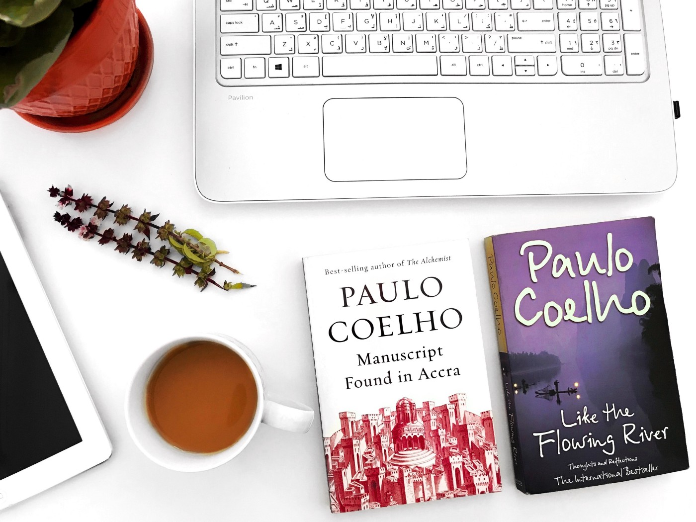Two Paulo Coelho books with a laptop on a table.