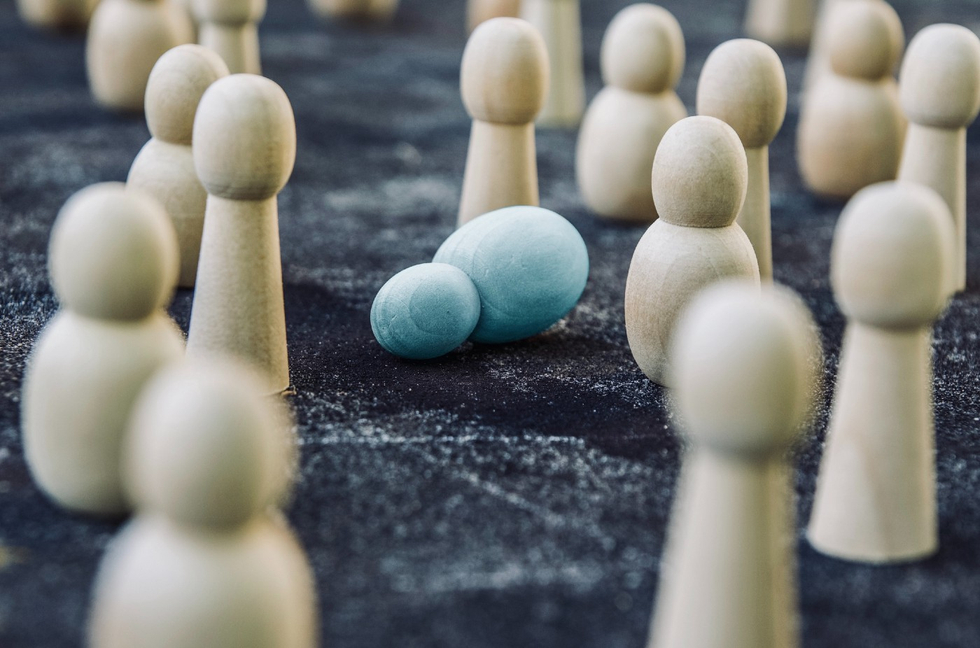 A round blue fallen pawn among a group of upstanding white pawns and bishops and rooks.