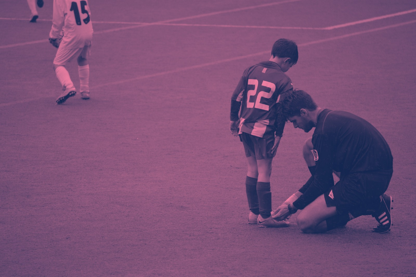 Man tying young soccer player's cleat