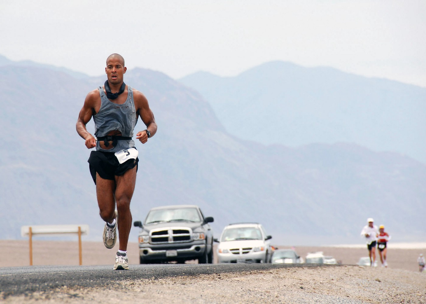 David Goggins running through Death Valley, California. He's running on the paved road, wearing a grey tanktop, black shorts and white sneakers. In the far back there are two runners. The landscape is mountaneous. A row of cars is visibible.
