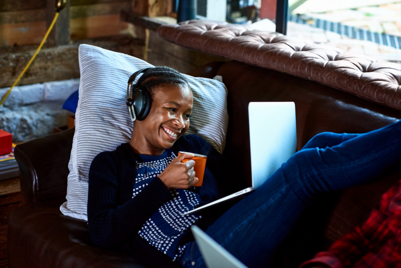 Smiling Black woman with headphones on looking at her computer with a cup of coffee in her hand.