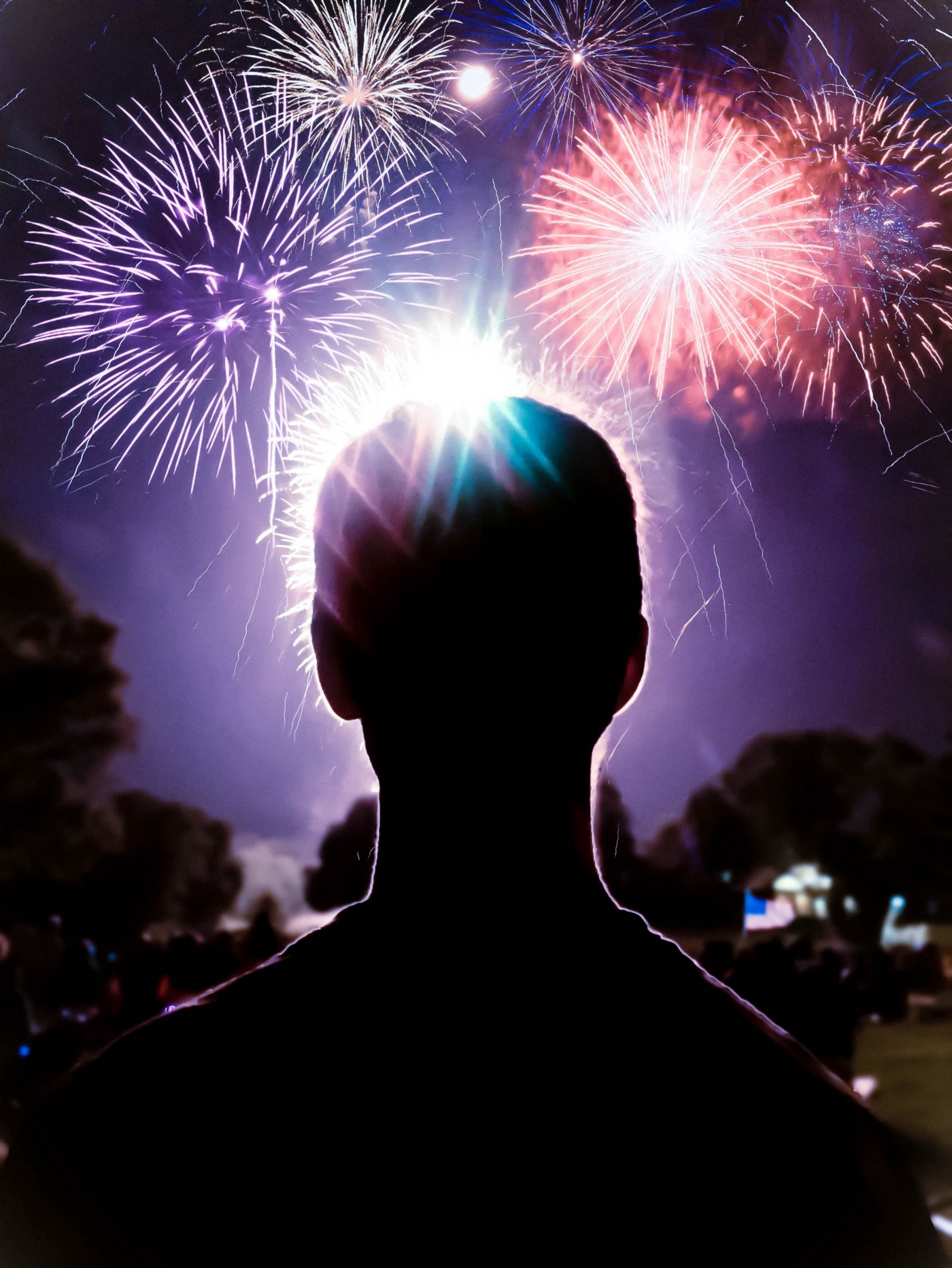 Outline of a man in the dark with the sky above him lit up by many large fireworks. Sky is a dark purple color.