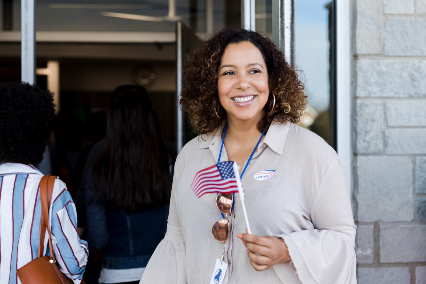 """Latina woman holding a little American flag, she has a """"Voted"""" sticker on her shirt."""