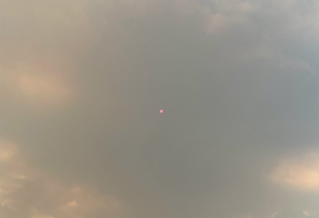 Sky thick with what looks like clouds but is actually a smoke plume from a forest fire. A small red shiny dot is visible in the center of the photo, which is the sun.