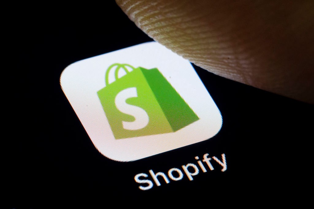 A logo of Shopify on a smartphone app that a finger is about to press.