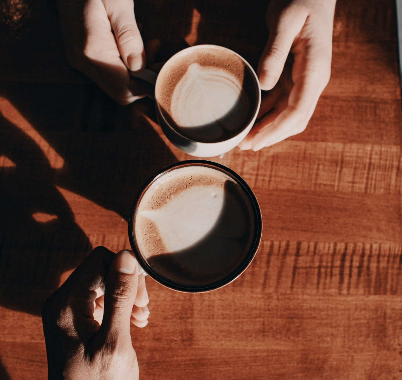 Two hands holding coffee cups on a table.
