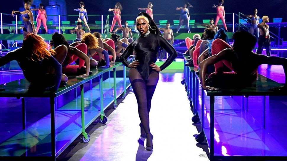 Shea Couleé walks the runway of the Savage X Fenty virtual show amidst dancers in a multi-colored stage