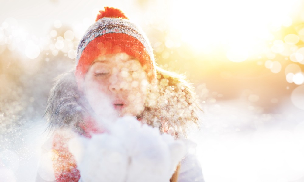 Young white woman in a snowy field wearing winter pompom hat, warm hooded ski jacket, blowing snow from white fluffy mittens