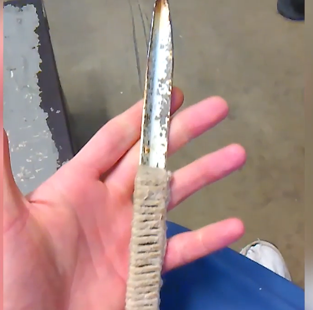 A homemade knife, covered in rust, its handle made of wrapped string or fabric. It is held in a hand to show to the camera.