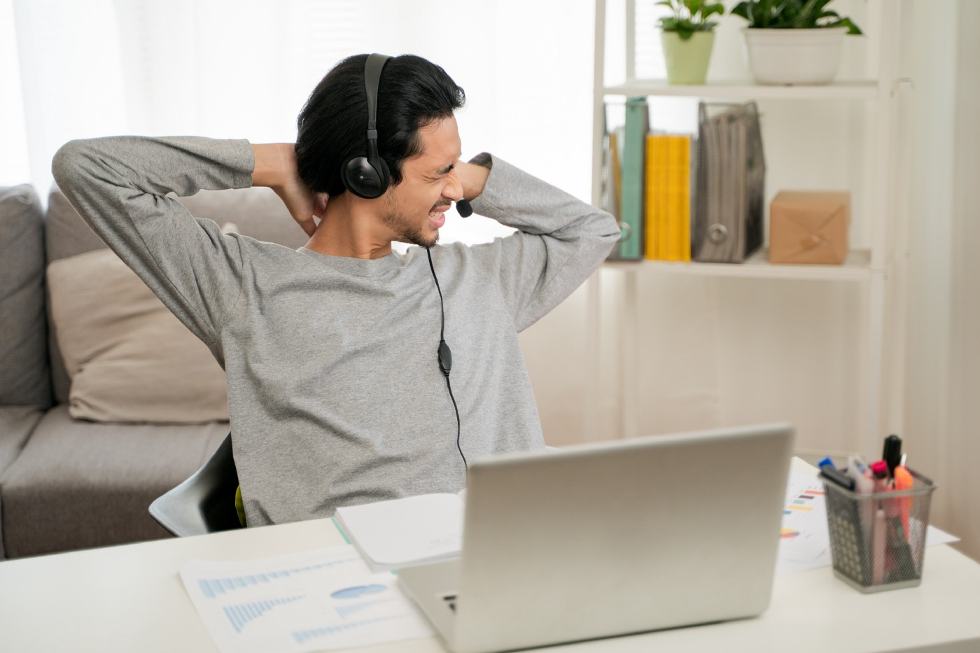 A young man experiencing stress after a video conference on his laptop, working from home.