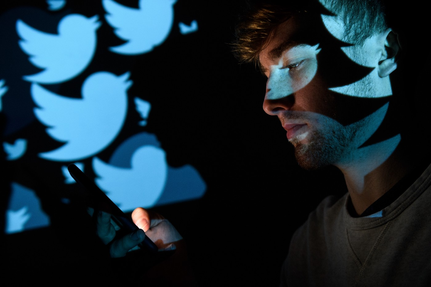 In this photo illustration, the logo for the Twitter social media network is projected onto a man's face.