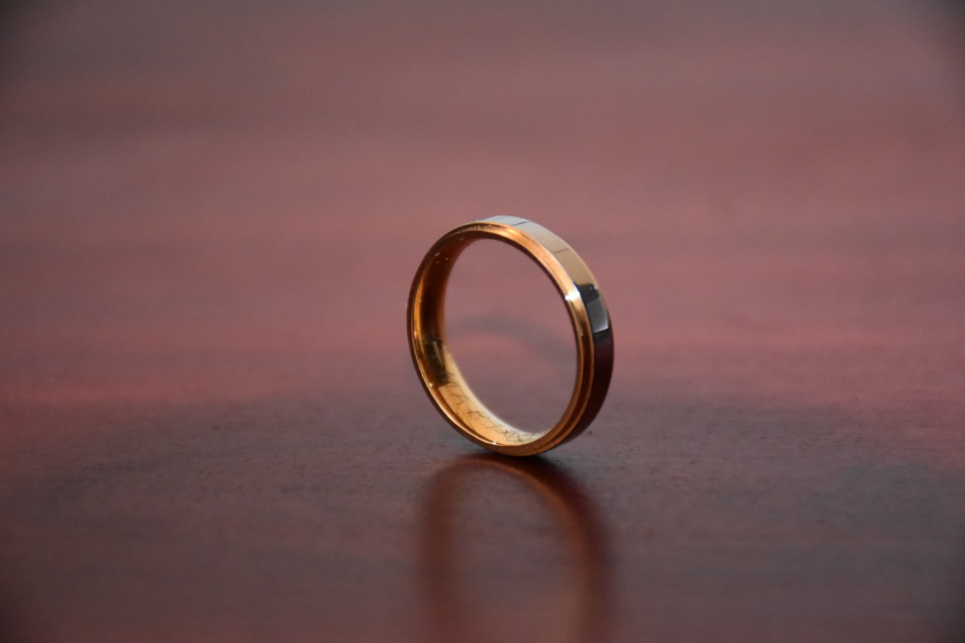 A plain gold ring on a wooden surface.