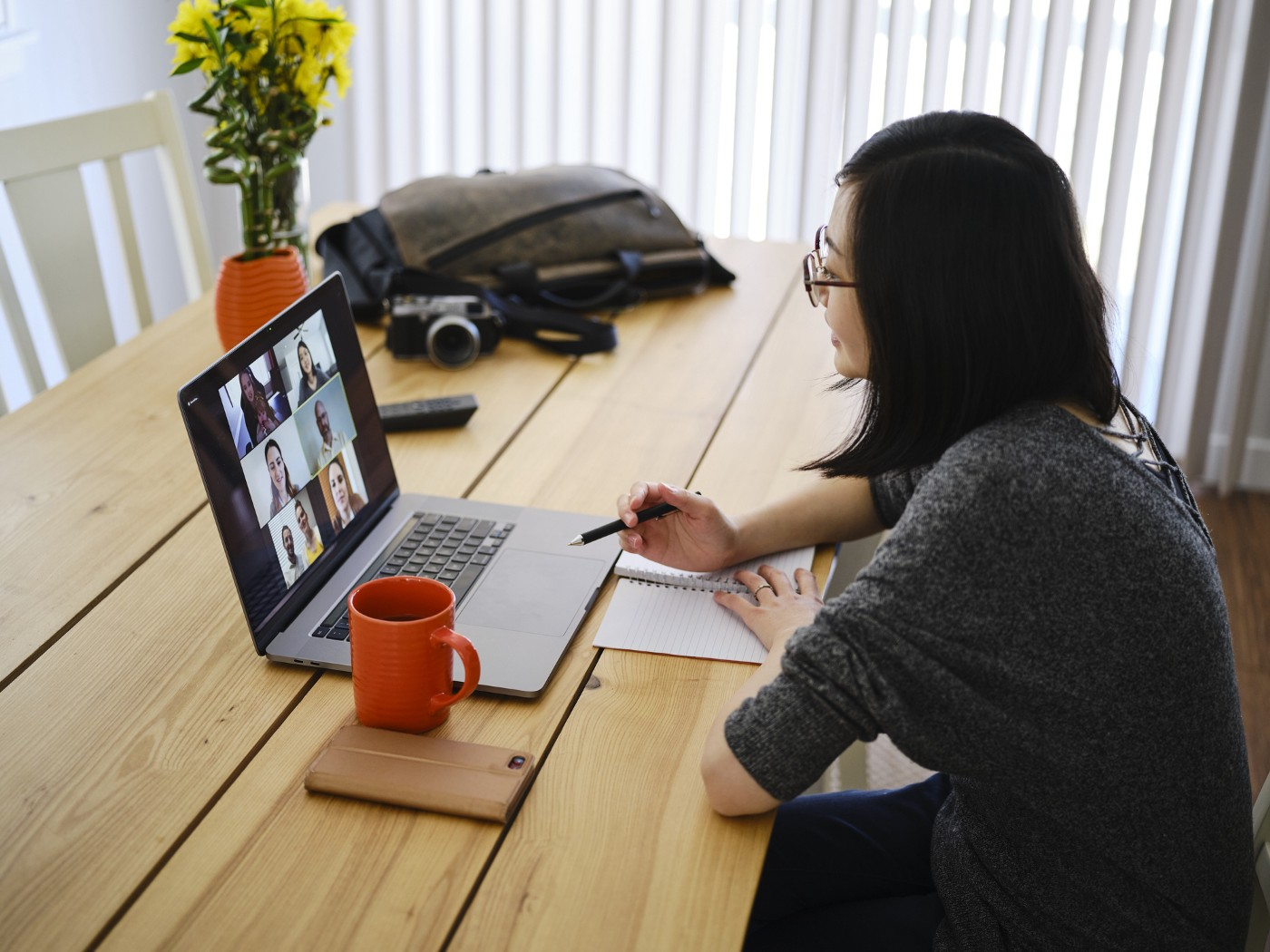 A woman working at home participating in a team video conference call.