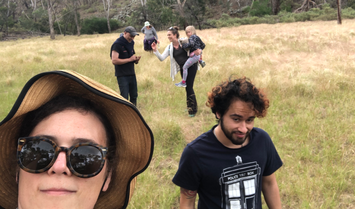 A group of people walk across a field towards the camera.