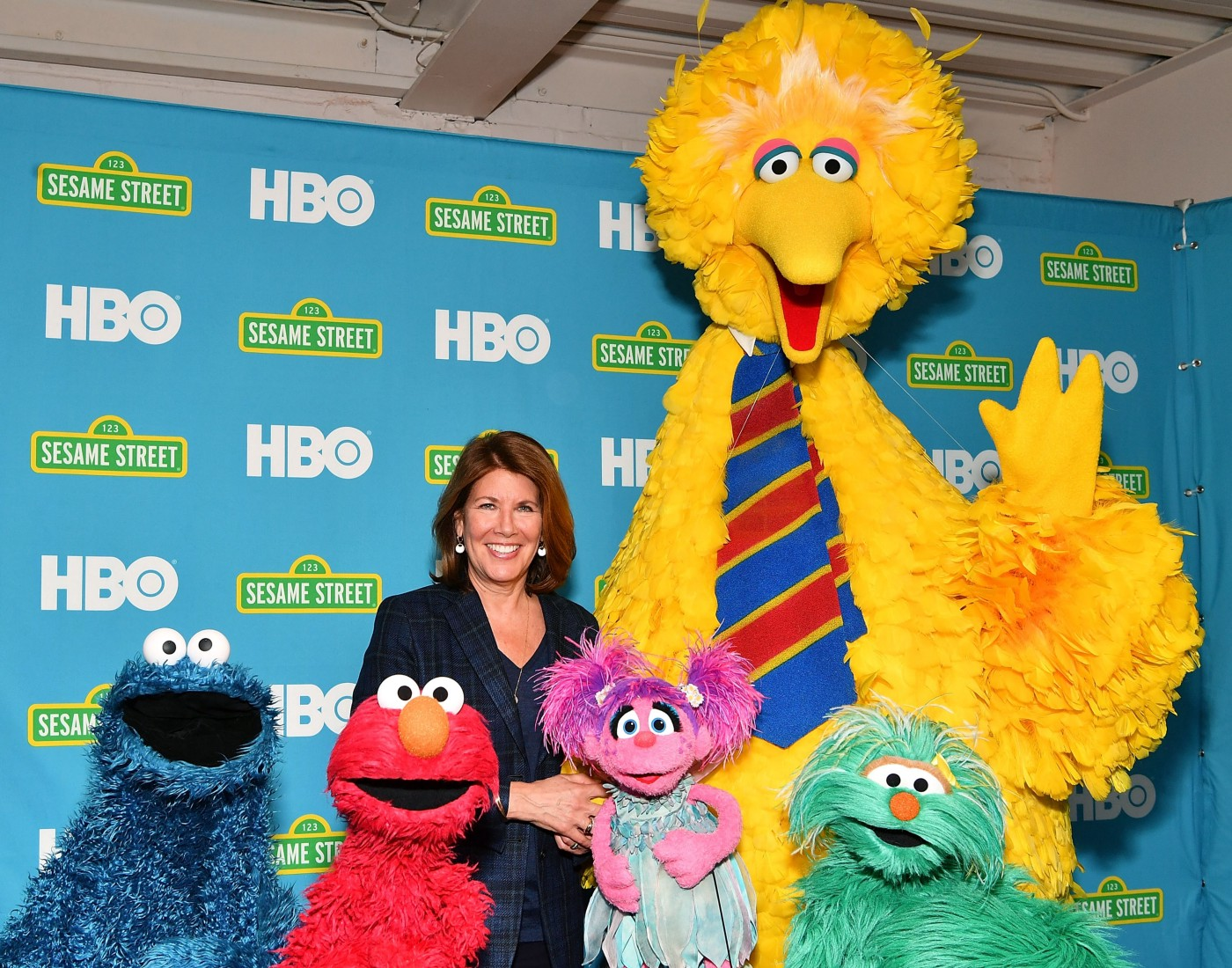 Sherrie Westin at the HBO Premiere of Sesame Street's The Magical Wand Chase, posing with Big Bird, Elmo, and Cookie Monster.