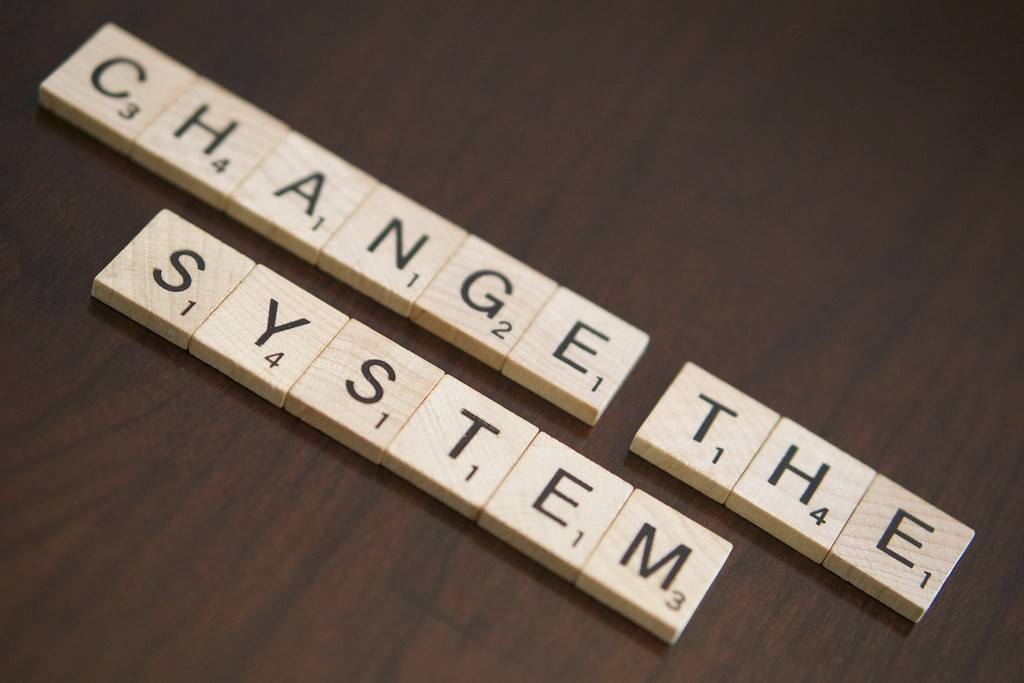 """Scrabble tiles spelling out """"change the system"""" sit on a wooden table."""