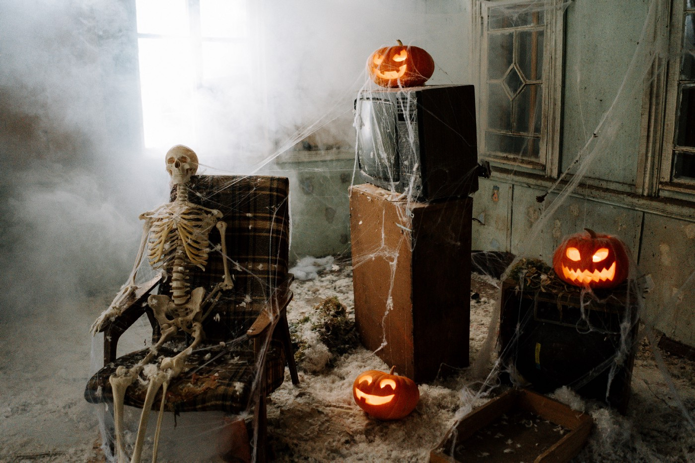 Skeleton and pumpkins and cobwebs