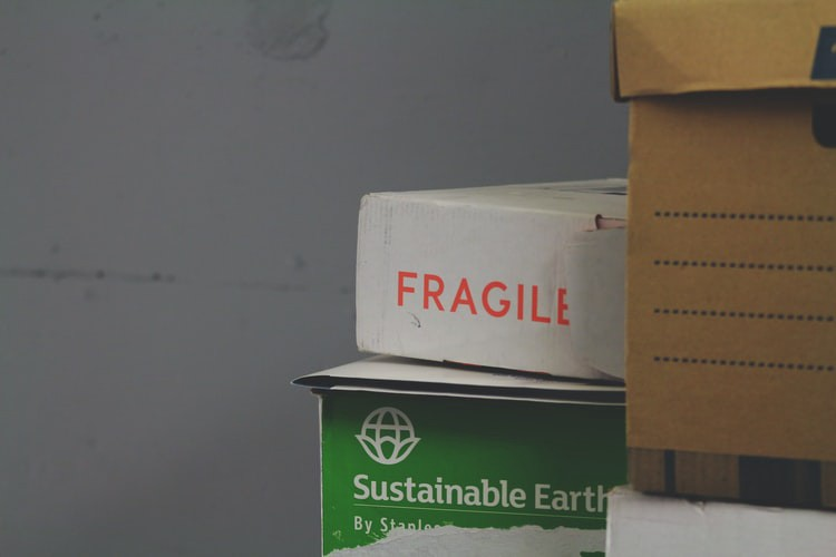 """Pile of moving boxes in a truck with a big white one that says """"Fragile"""""""
