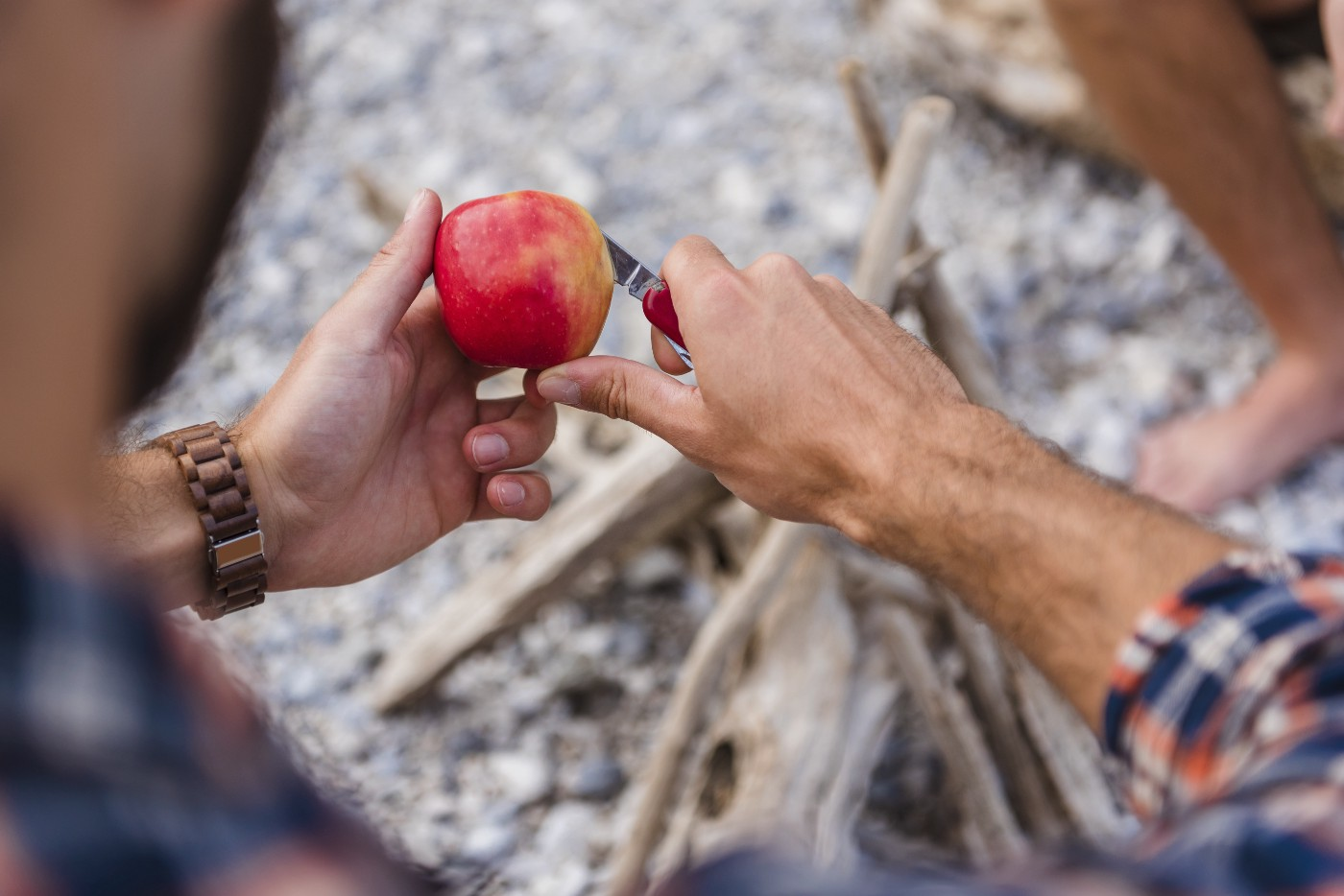 Person using pocket knife to peel apple skin.