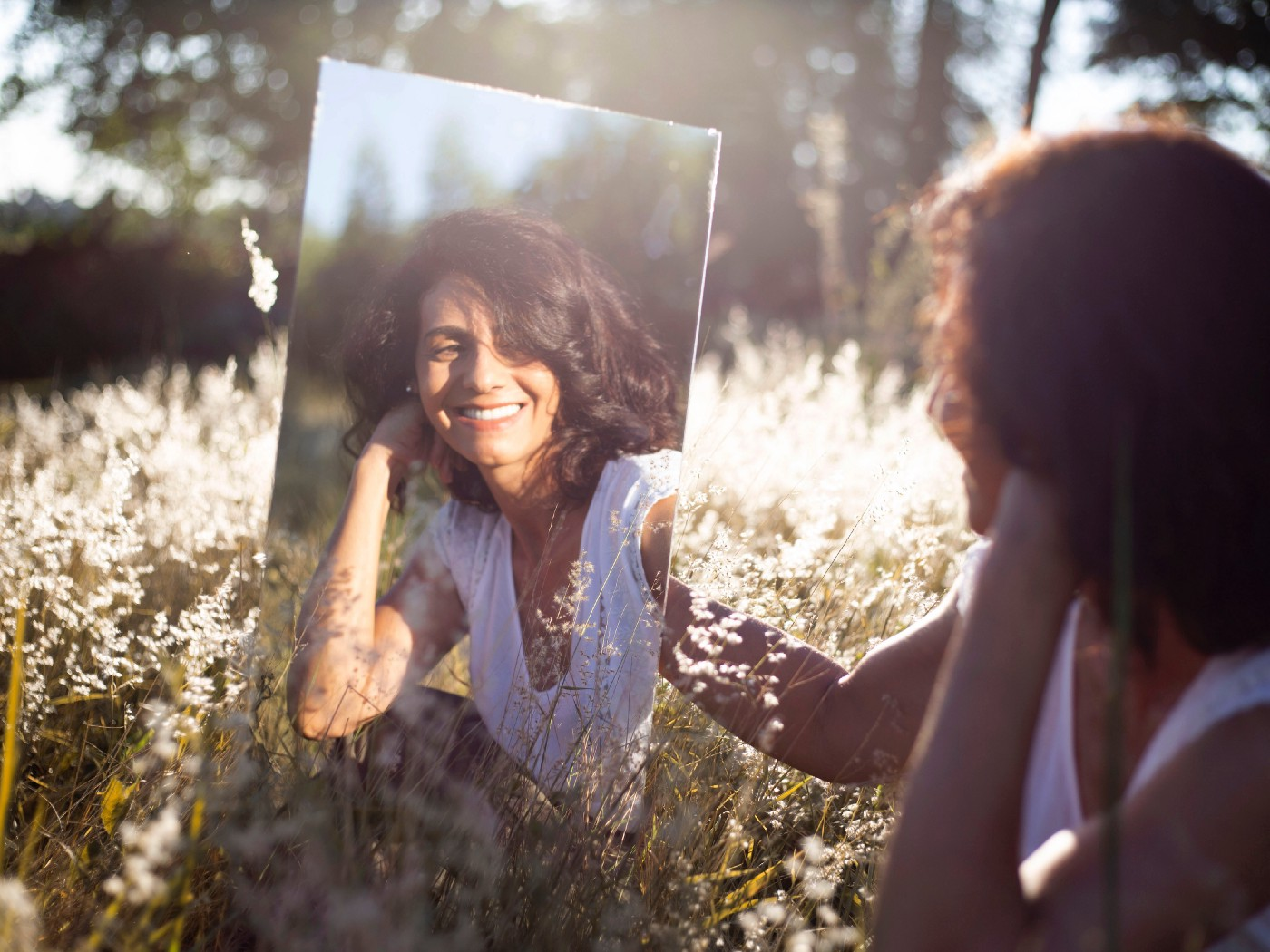 the image shows a young woman sitting in long grass holding up a mirror and smiling at her reflection