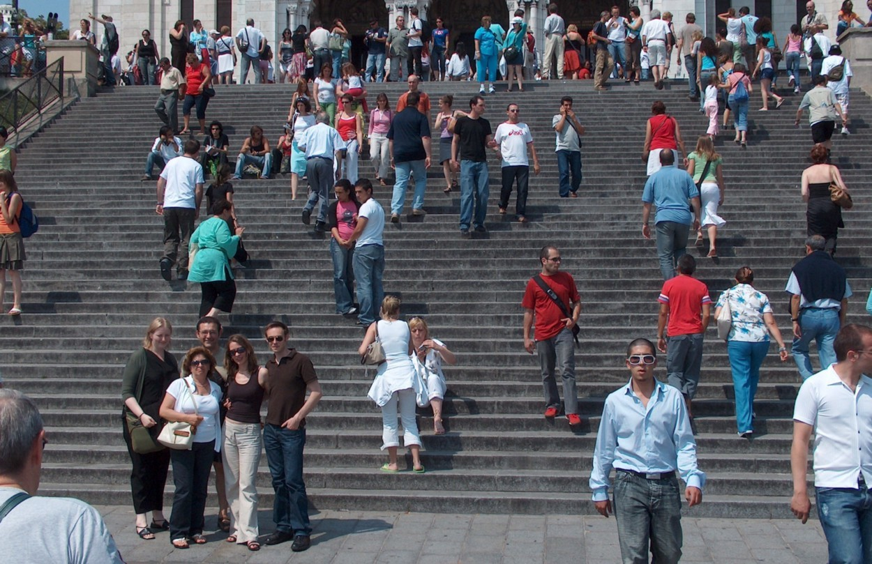 Large staircase in front of a building filling the picture with people walking up and down