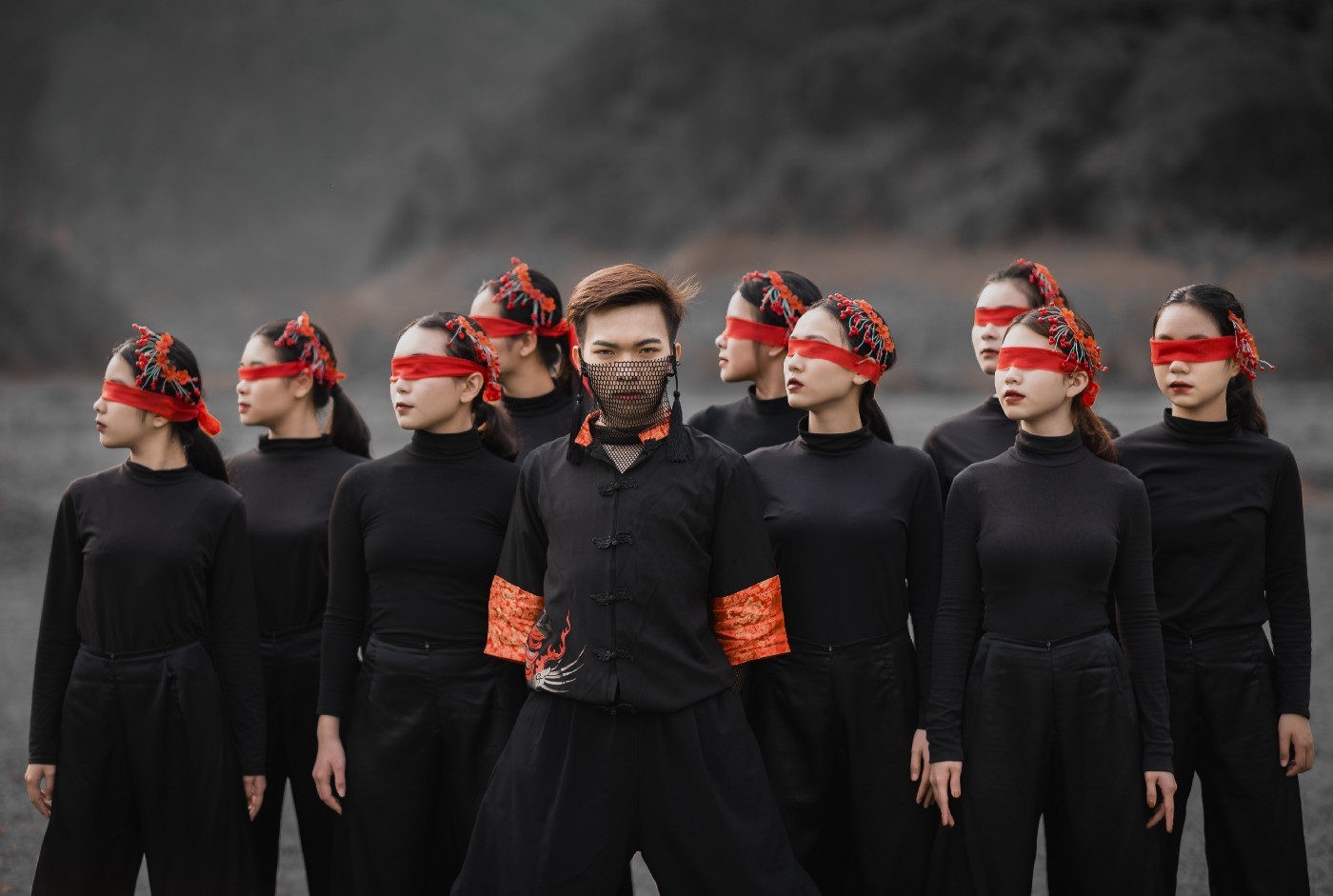 A man surrounded by women wearing black clothes and red blindfolds stand together as a group
