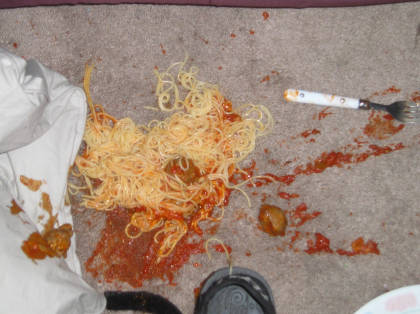 Spilled spaghetti with a fork on a cement floor
