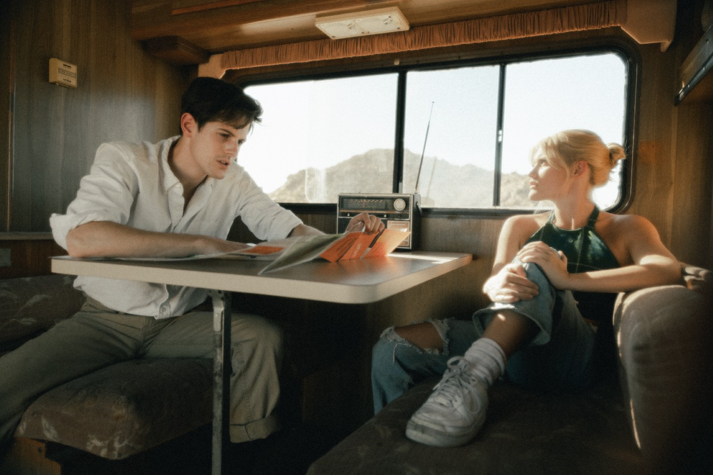 Two people talk in an RV.