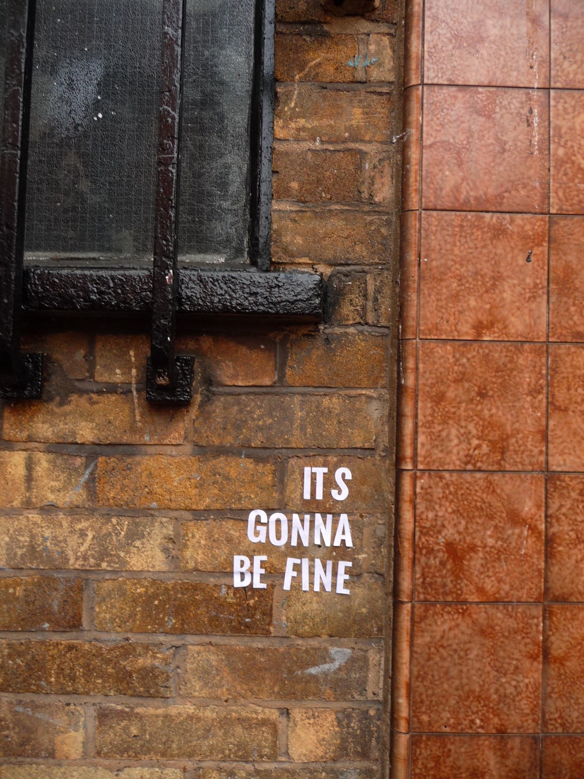 """The words """"It's Gonna Be Fine"""" glued on a brick wall"""