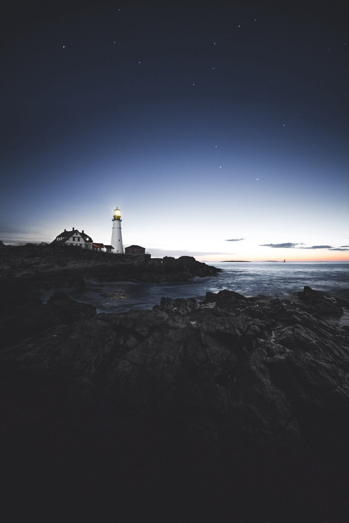 A lighthouse exudes a soft beam as dusk approaches against the backdrop of a dark, rocky ocean.