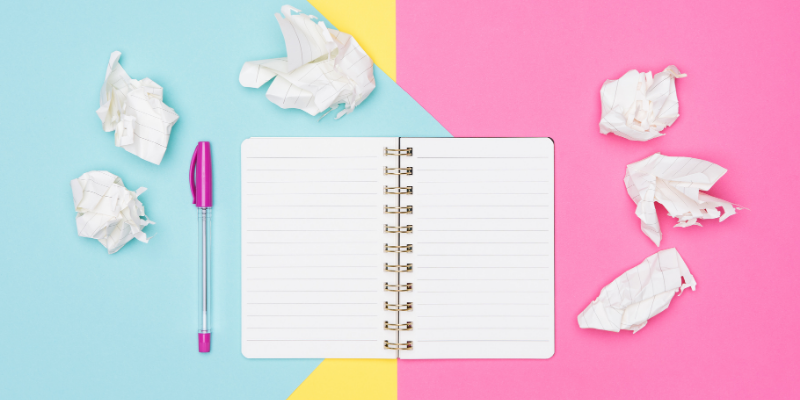 Notepad, pen, and crumpled paper against a pastel background — The Ultimate List of My Favorite Writing Tools