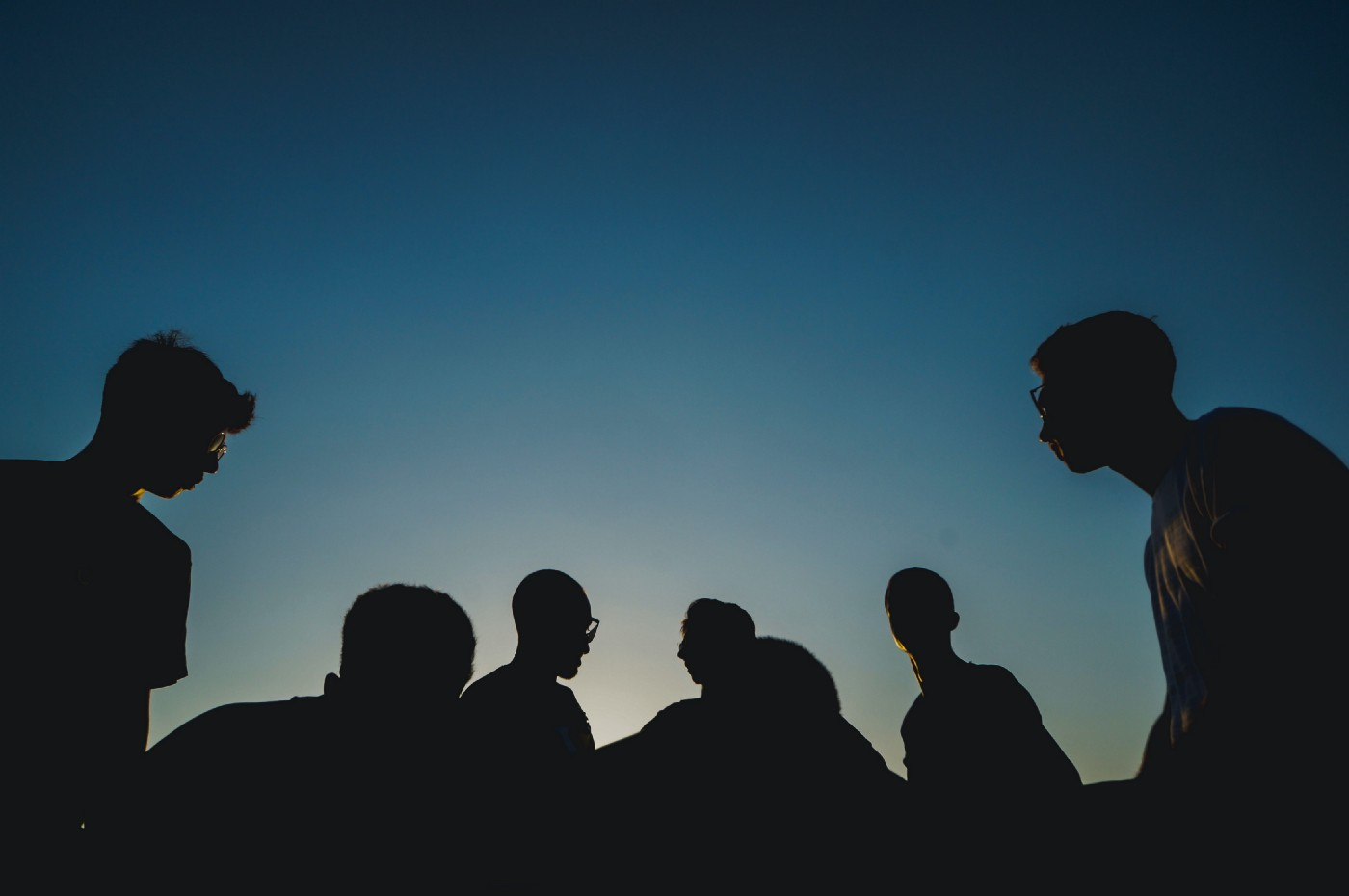 Silhouette of a group of people sat together (https://unsplash.com/@papaioannou_kostas)