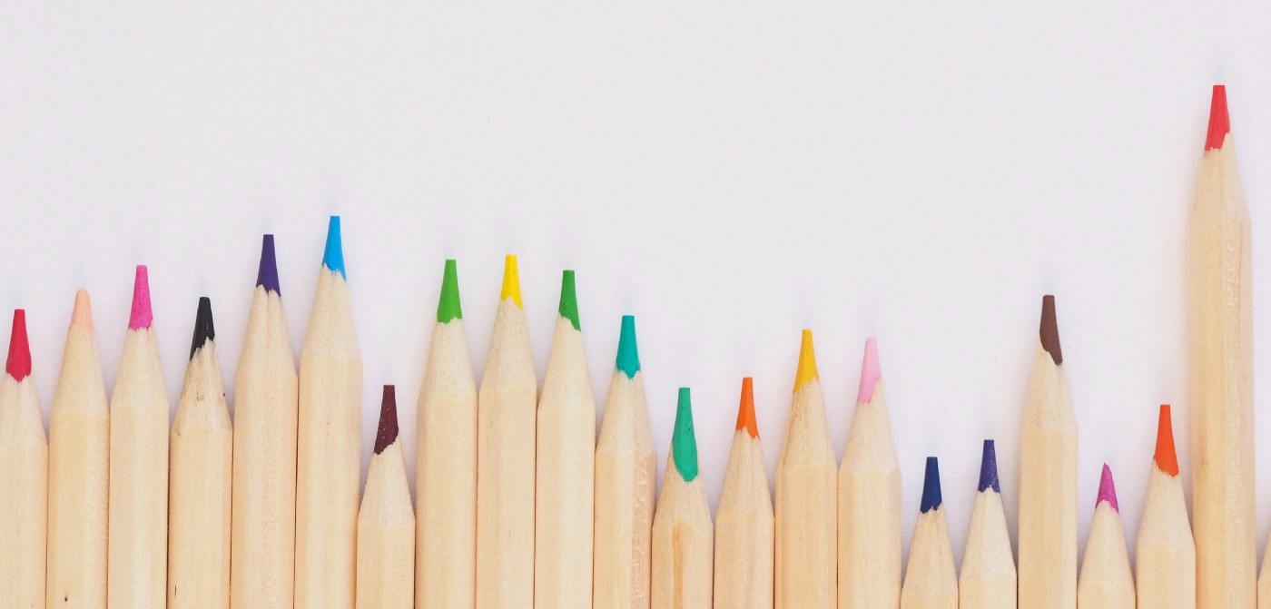 Photo by Jess Bailey on Unsplash showing a line of brightly colored pencils lined up at different heights