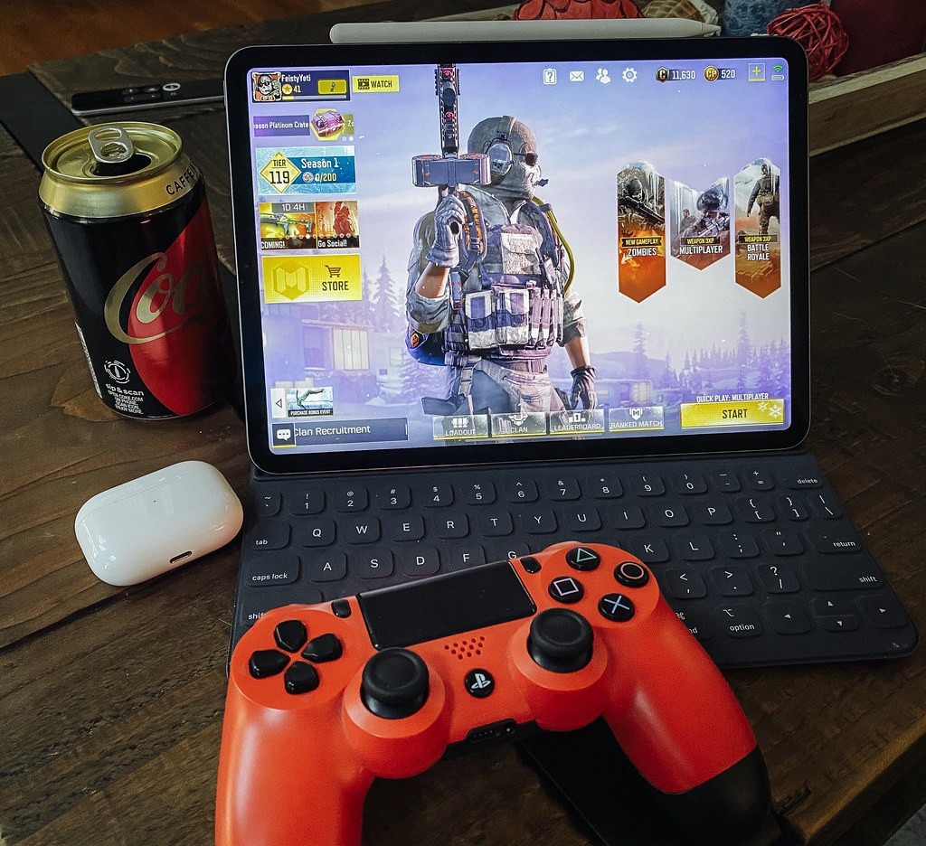 """iPad Pro 12.9"""" 2020 with PS4 Controller, Apple Airpods and a can of drink"""