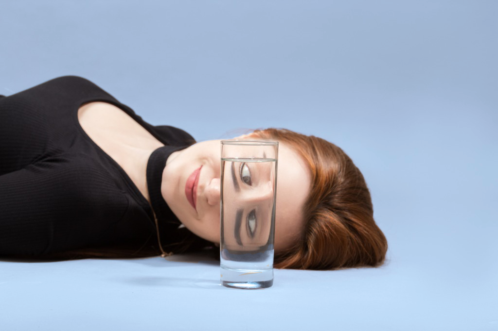 Woman looking through a glass of waters with eyes crossed.