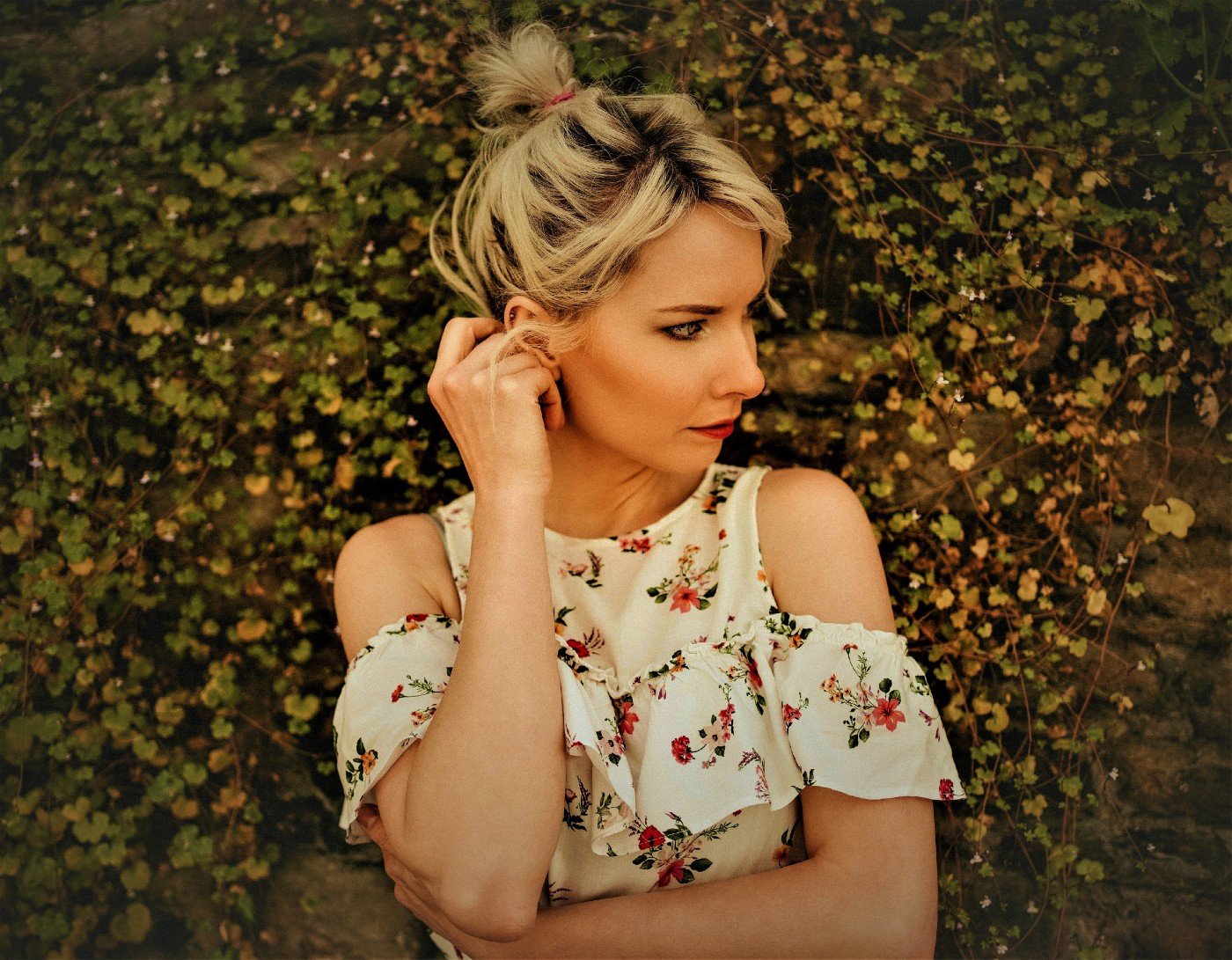 pensive woman with blonde hair tied up on her head wearing flowered dress and holding right ear with right hand