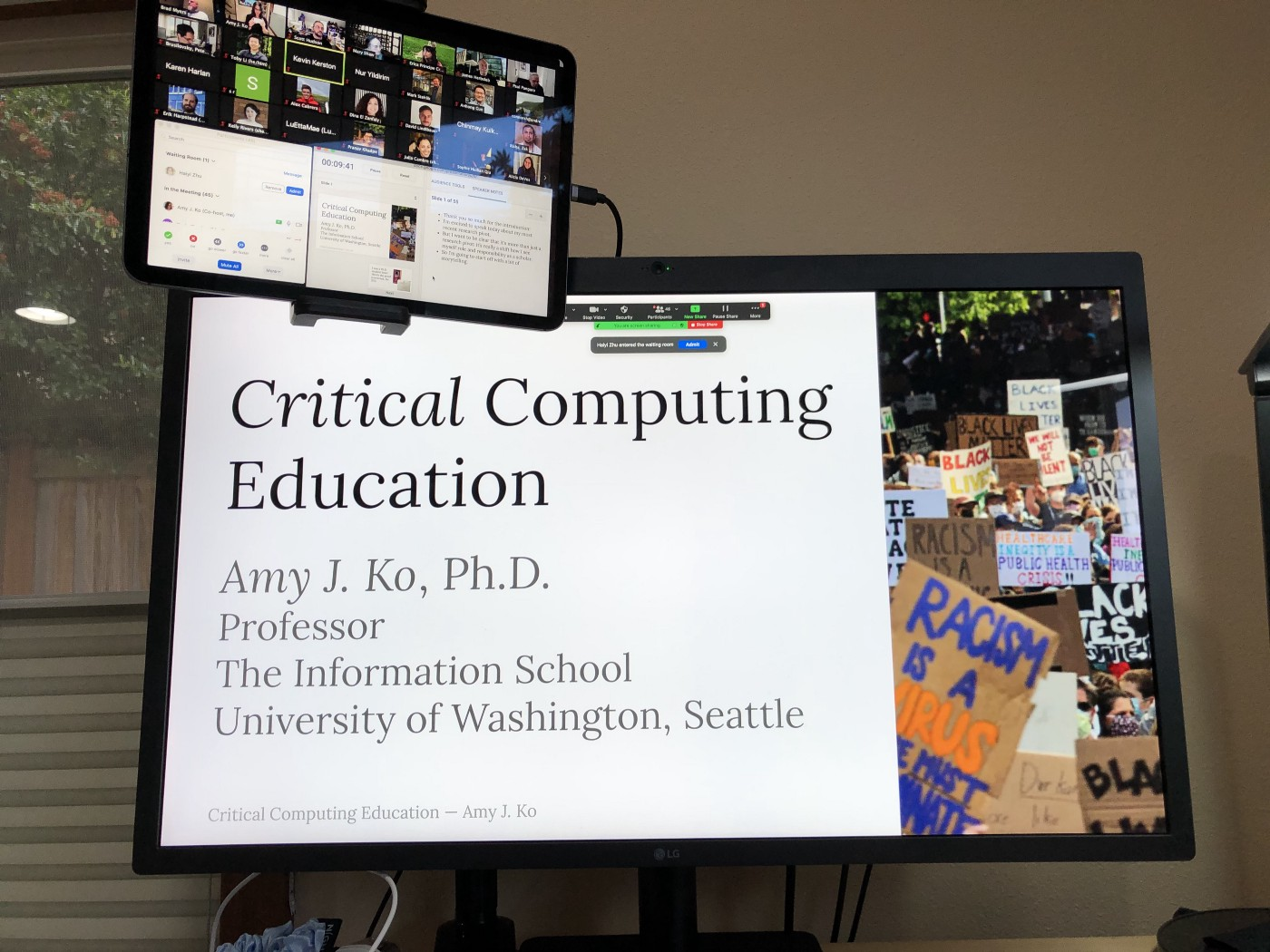 "A photograph of a display showing a slide titled ""Critical Computing Education"", with an iPad hovering above showing Zoom."