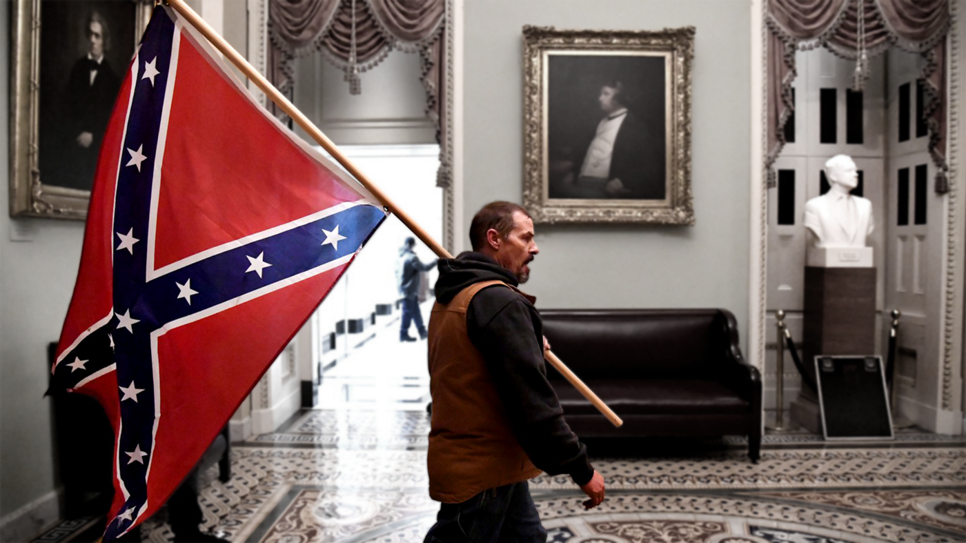 A man stands in the capital holding a confederate flag.