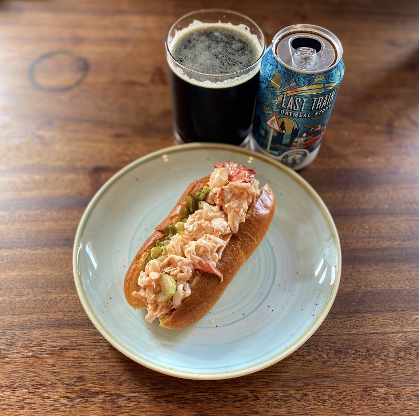 Photo of a lobster roll on a plate with a cup of beer next to it.