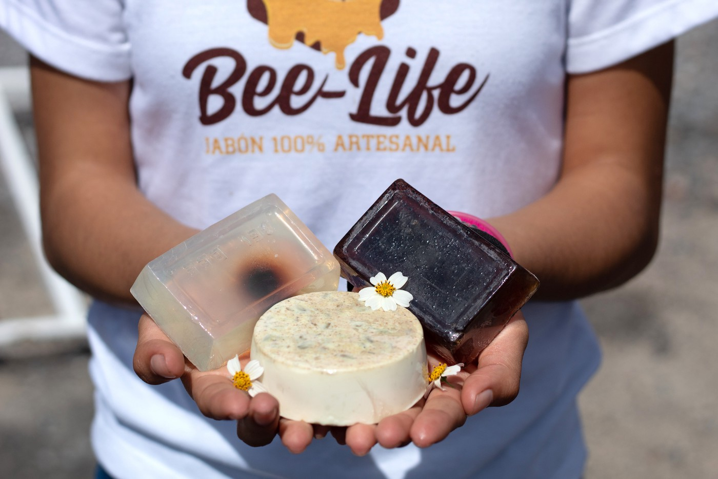 A teen girl holding Bee-Life Brand soaps in her hands.