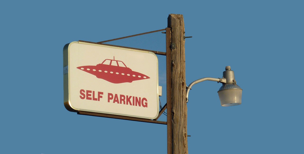 """Wooden telephone pole with a streetlamp attached to one side and a sign attached to the other showing the image of an alien spacecraft and the words """"Self Parking"""""""
