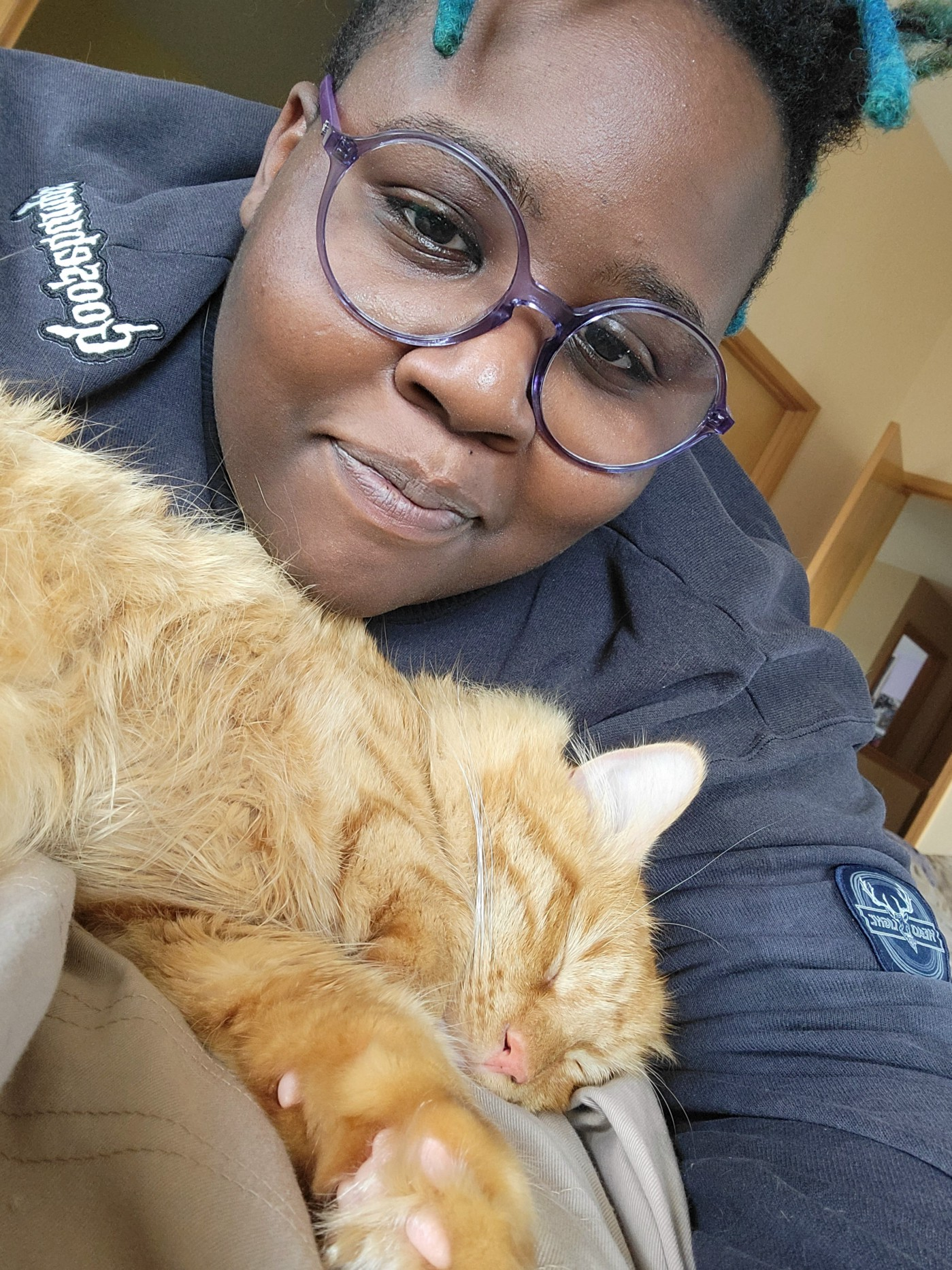Building a Community on Medium by Aigner Loren Wilson article cover. Image of author, Aigner, behind a sleeping orange kitten. She is smiling.
