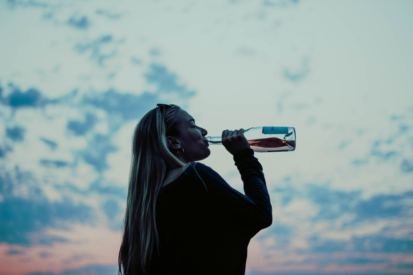 woman drinking from bottle at sunset