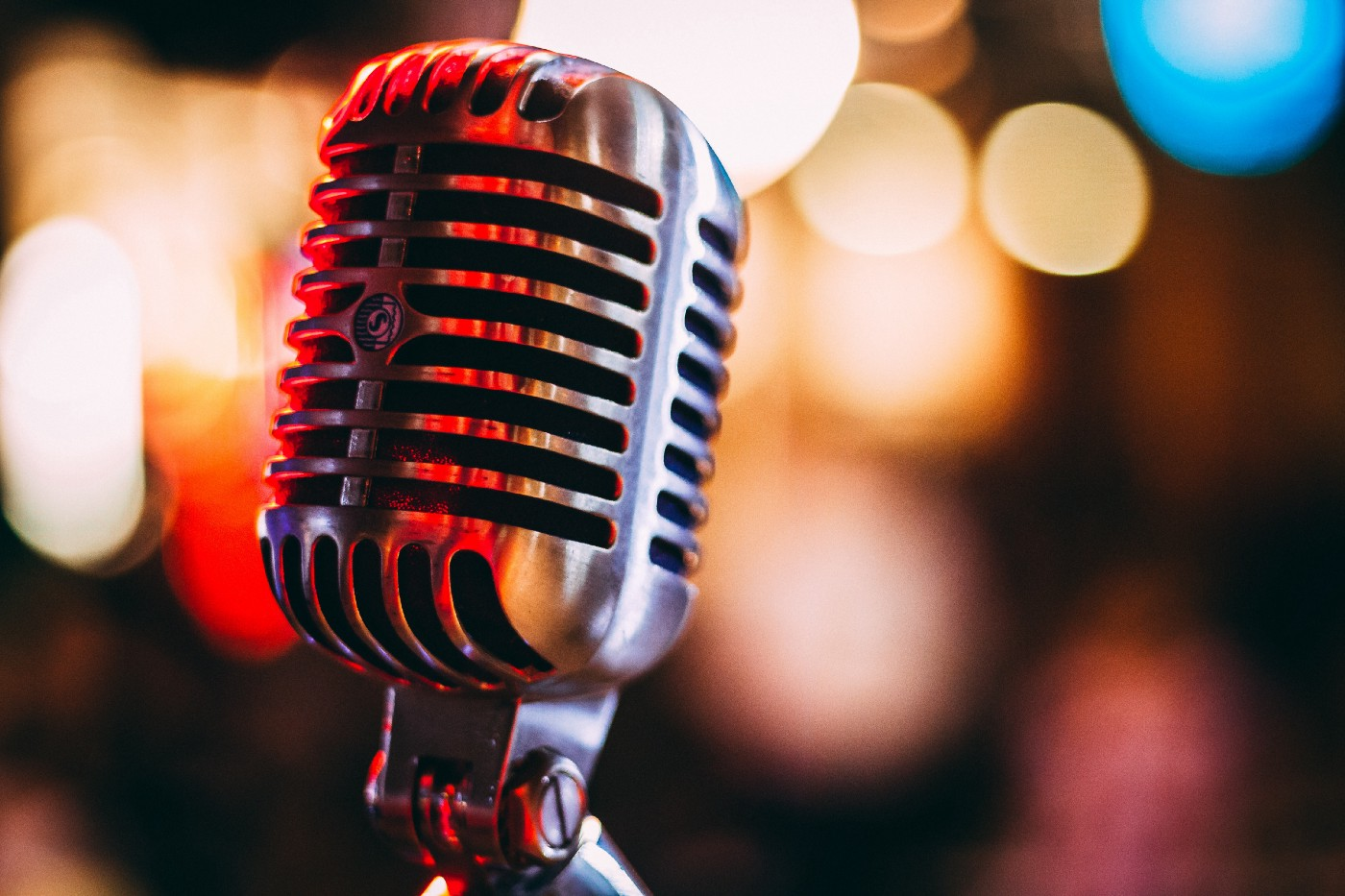 A microphone sits against a lit backdrop.