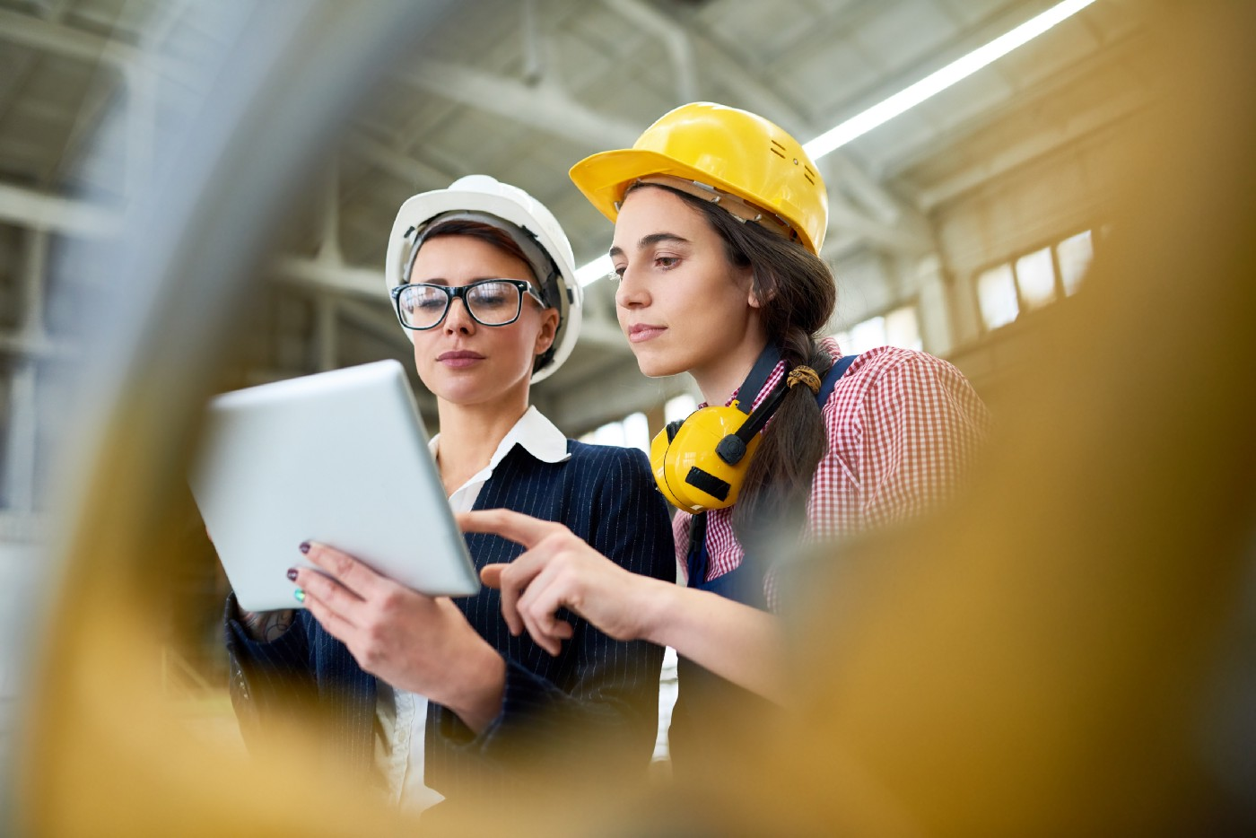Two women in hard hats looking at a tablet in a warehouse setting