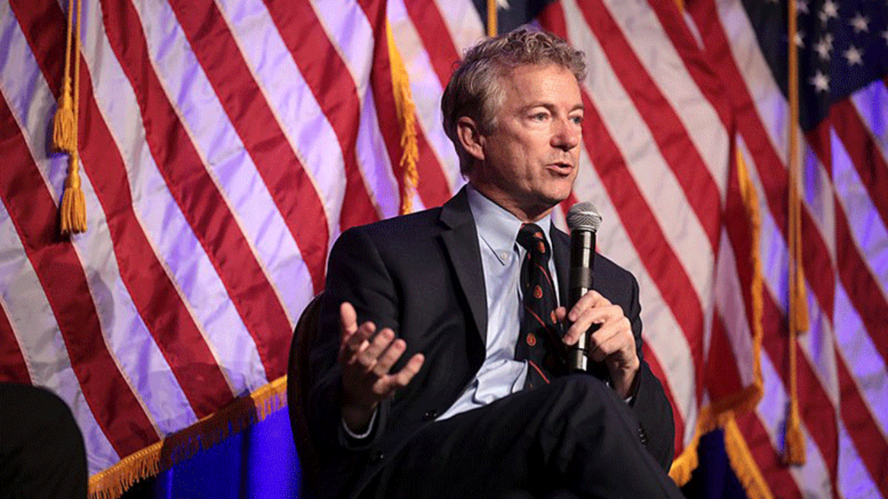 Senator Rand Paul sitting down with a microphone in hand with an American flag behind him.