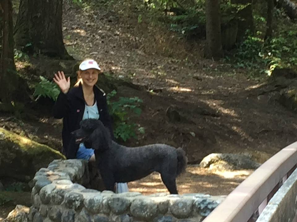 Me waving Hi, seated on a low stone wall next to a bridge with my beloved black standard poodle while on a camping trip. Trees and a path are in the background.