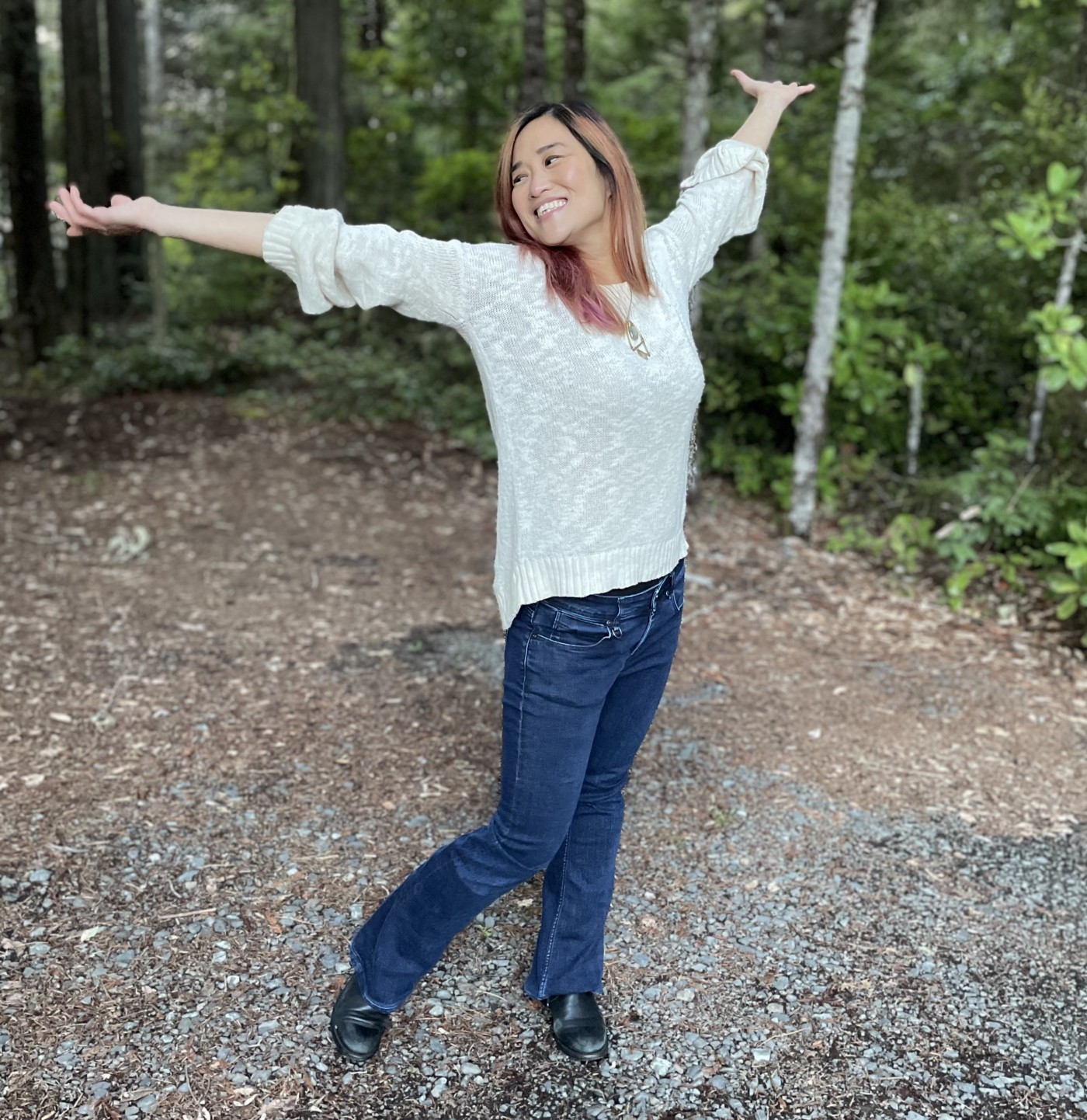 Photo of the author, hands raised mid-twirl, in a forest setting