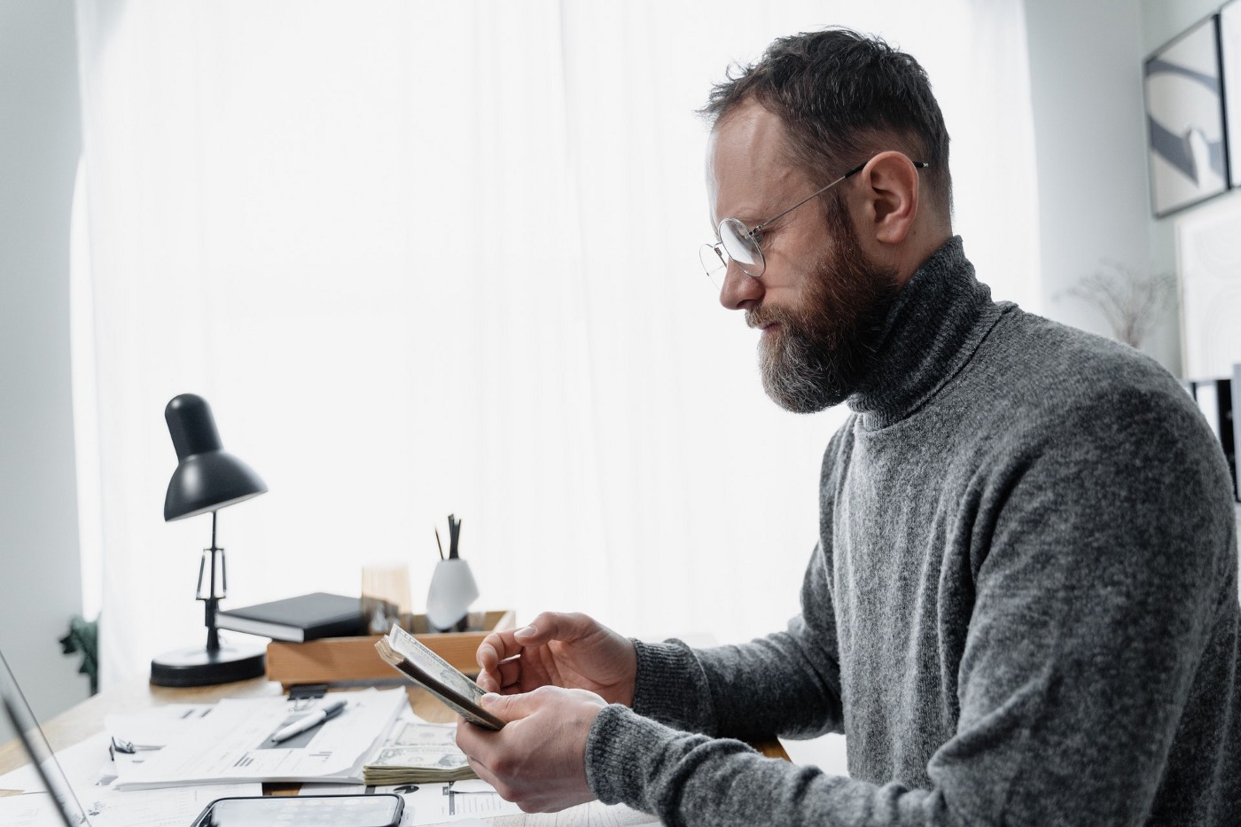 Man with a beard counting money while sitting at his desk