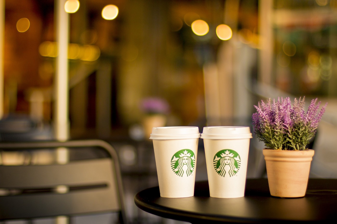 Two Starbucks coffee cups on a black table with a purple flowered plant sitting next to them